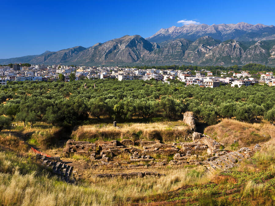 Remains of ancient Sparta, ruins of theater. The modern city and fragment of the Taygetus mountain in the background