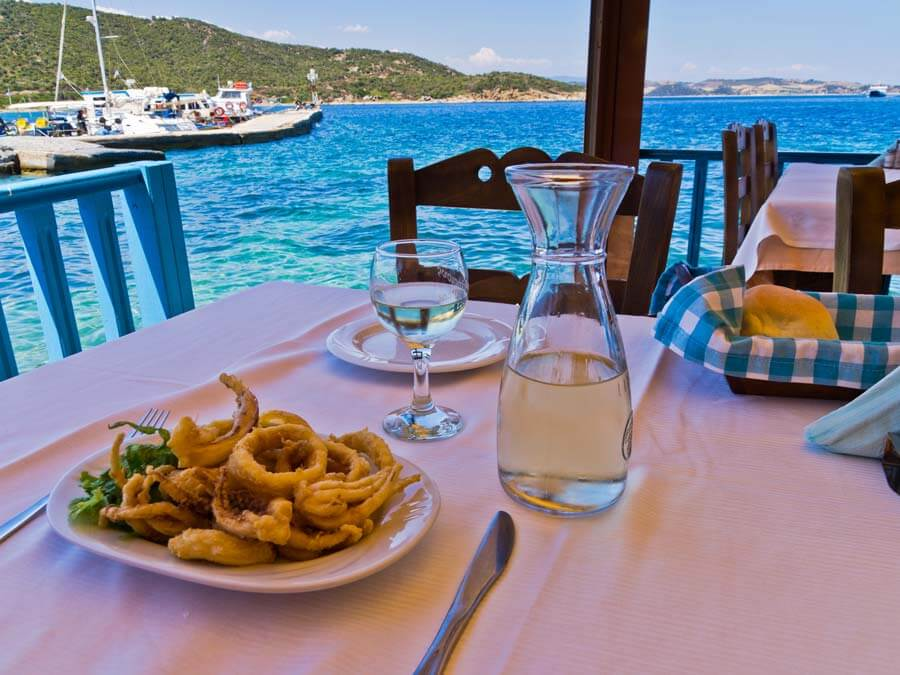 Seaside taverna with fried squid and wine on the table