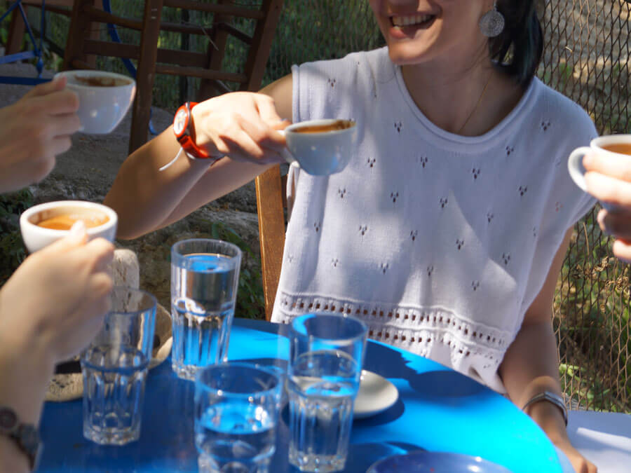Friends enjoying Greek coffee during a food tour in Athens